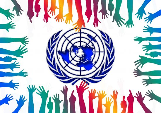 UN logo with multicolored hands reaching toward it