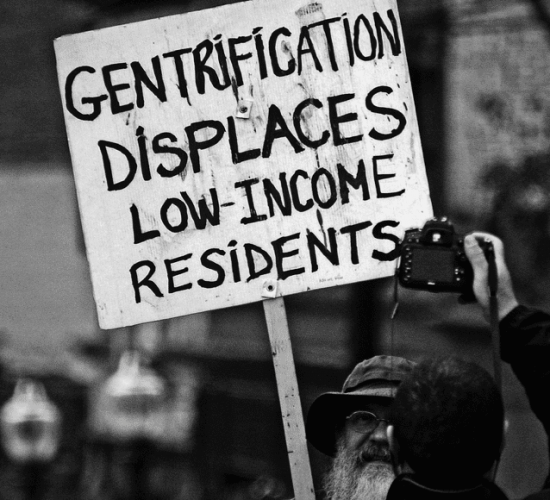"""Protestor holding a sign that reads """"gentrification displaces low-income residents"""""""