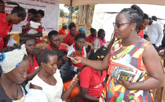 Members of the Center for Health, Human Rights and Development (CEHURD), a Ugandan NGO, distribute handbooks to adolescent girls and young women to guide them in enforcing the legal empowerment and social accountability strategy in pursuit of the right to health.
