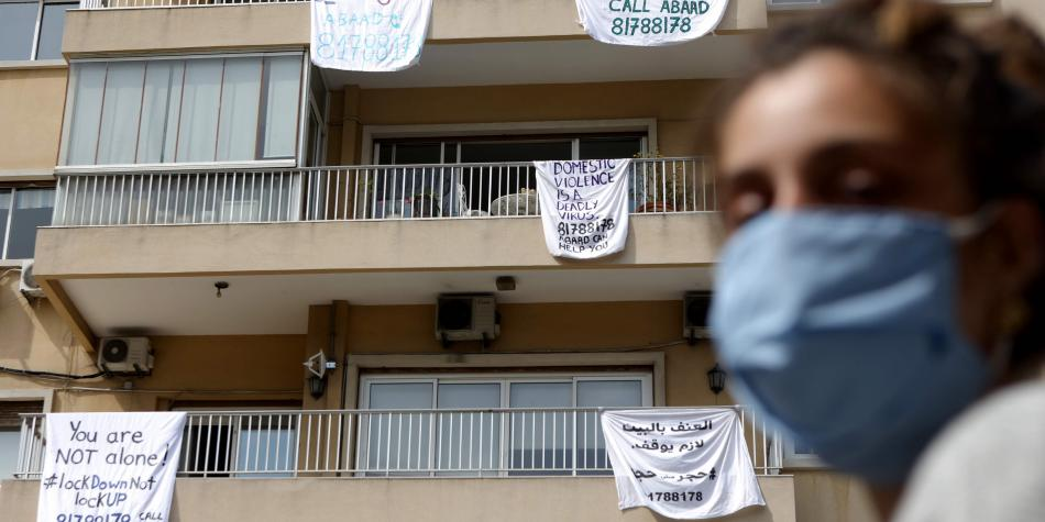 Apartment building with sheets hanging over the balconies, each displaying an anti-domestic violence message or hotline.