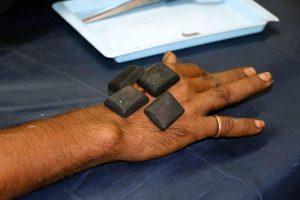 hand with black stones
