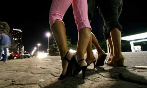three women stand on the street at night, wearing high heels