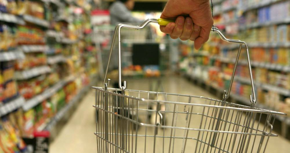 hand carrying a grocery basket in a supermarket aisle