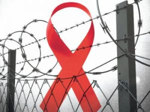 Red AIDS awareness ribbon behind a barbed wire fence