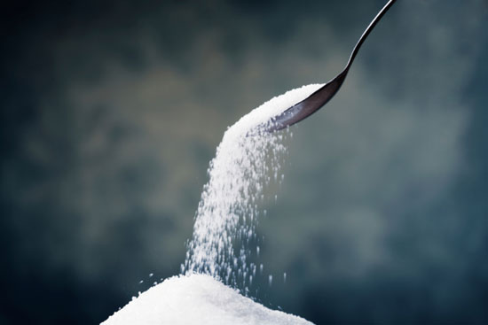 Sugar falls from a spoon into a pile of sugar below.