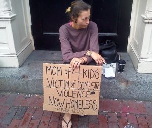 Photo of a homeless woman with a sign
